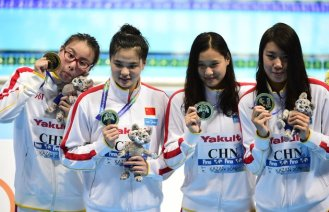 Team China celebrates its gold medal during the podium ceremony for the women's 4x100m medley relay swimming event at the 2015 FINA World Championships in Kazan on August 9, 2015. Shi Jinglin, Lu Ying, Fu YuanHui and Shen Duo competed in the event. AFP PHOTO / ALEXANDER NEMENOV (Photo credit should read ALEXANDER NEMENOV/AFP/Getty Images)